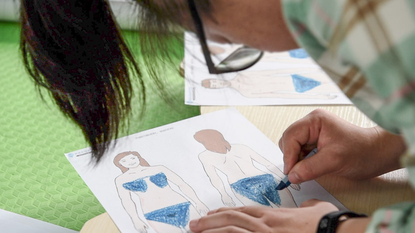 A young woman uses a crayon to color over parts of a woman's body during a sex education class in Guangzhou, Guangdong province, April 16, 2017. He Tingtong for Sixth Tone