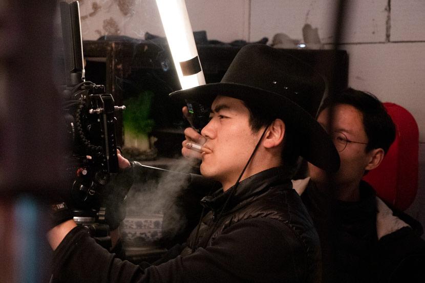"""A cameraman smokes as he shoots a """"short drama"""" in Hengdian Town, Zhejiang province, Jan. 15, 2020. Kenrick Davis/Sixth Tone"""