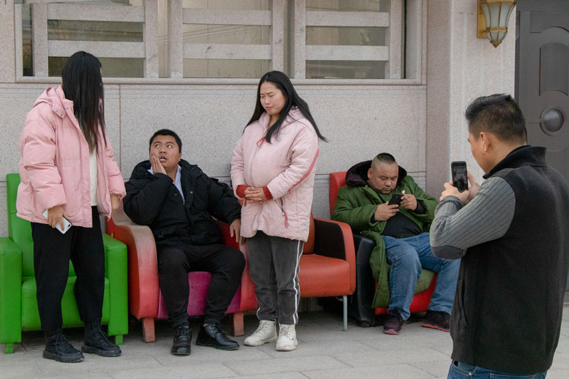 Several short-video makers, one pretending to be pregnant, film a comedy skit in Hengdian Town, Zhejiang province, Jan. 13, 2020. Kenrick Davis/Sixth Tone
