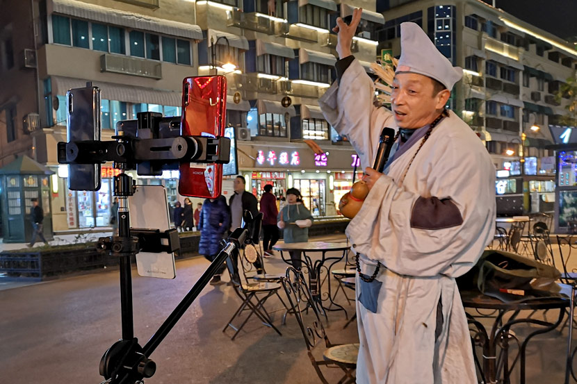 A livestreamer wearing a monk outfit performs traditional songs in Hengdian Town, Zhejiang province, Jan. 14, 2020. Kenrick Davis/Sixth Tone