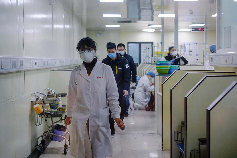 Medical workers walk through an outpatient IV ward at Ruijin Hospital in Shanghai, Jan. 23, 2020. Wu Huiyuan/Sixth Tone