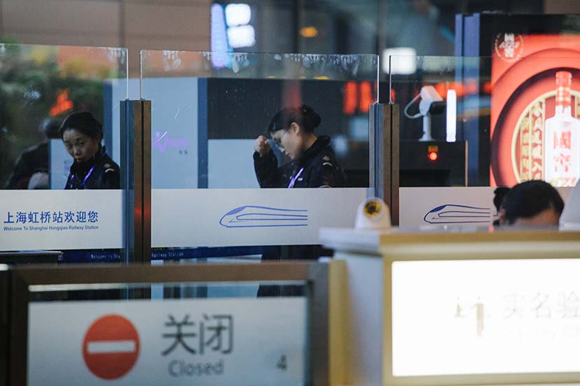 A security guard passes through a temperature screening checkpoint at Shanghai Hongqiao Railway Station, Jan. 22, 2020. Wu Huiyuan/Sixth Tone