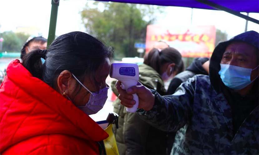 A medical worker takes a woman's temperature in a village near Nanchang, Jiangxi province, Jan. 26, 2020. Liu Zhankun/CNS