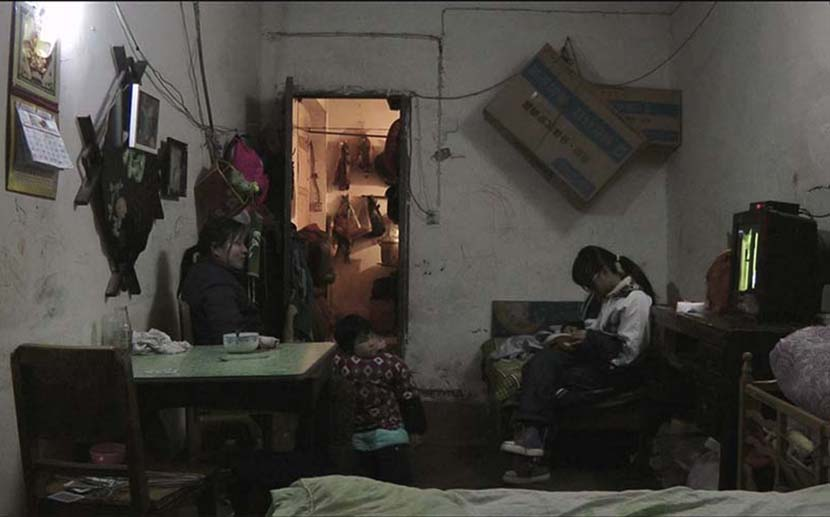 A mother and her two daughters in a small shared living area. Courtesy of Zhu Shengze