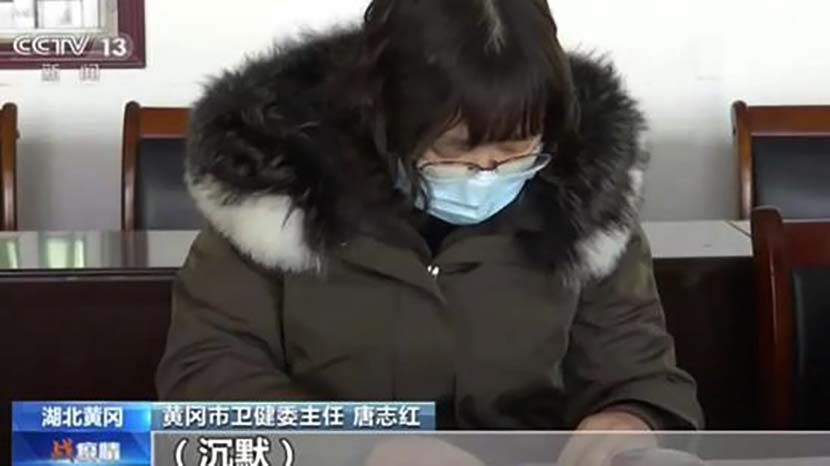 A screenshot from CCTV News shows the director of Huanggang's health committee during a meeting with the supervisory team from Beijing, which later recommended that she be removed from her post.