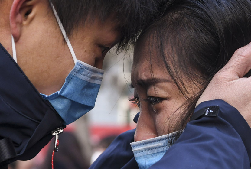 A medical worker (left), who is traveling to Wuhan to reinforce the city's overstretched hospitals, says goodbye to a family member in the northwestern city of Urumqi, Jan. 28, 2020. Wang Fei/Xinhua