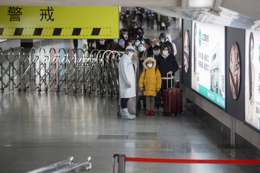 Passengers arriving in Shanghai wait to pass an infrared thermal imaging scanner, designed to identify those suffering from a fever, at Shanghai Railway Station in Shanghai, Jan. 31, 2020. Yi Chuan for Sixth Tone