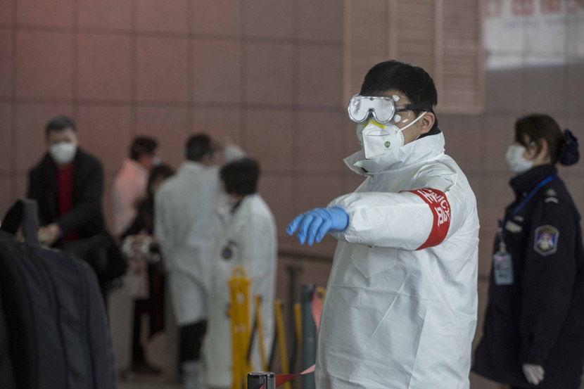 A worker in a protective suit directs passengers at Shanghai Railway Station in Shanghai, Jan. 31, 2020. Yi Chuan for Sixth Tone
