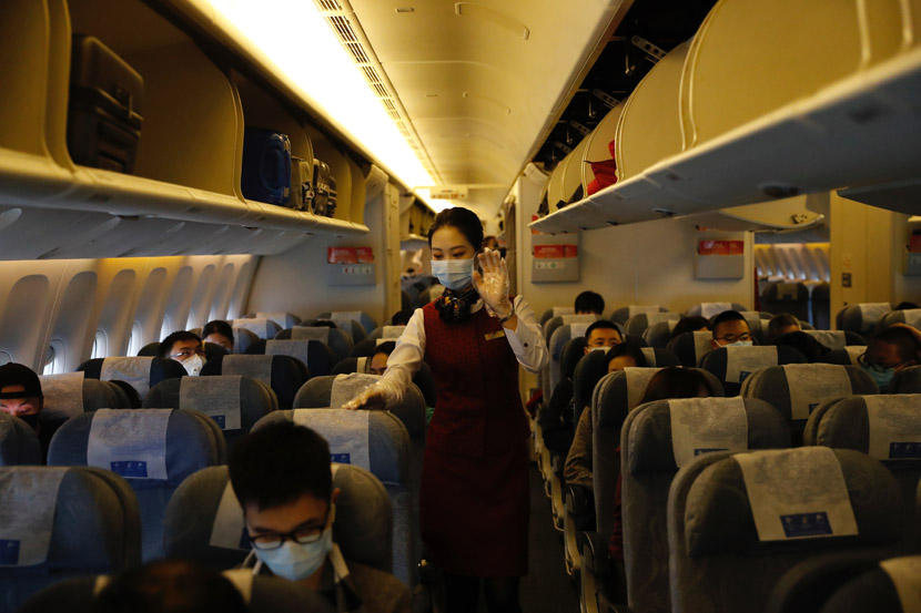 A flight attendant wearing a face mask assists passengers during a flight from Chongqing to Beijing, Jan. 29, 2020. Jiang Wenjie for Sixth Tone