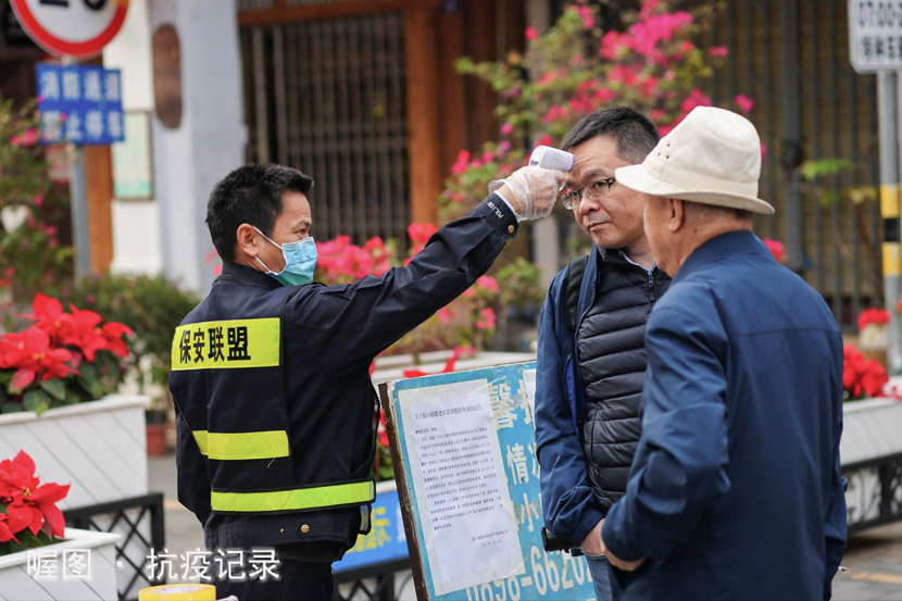 """A security guard tests the body temperature of a passerby in Haikou, Hainan province, Jan. 29, 2020. From """"Epidemic Resistance Record,"""" an online project featuring the work of photographers from several Chinese cities. Courtesy of Shun Zi via 喔图Alltuu"""