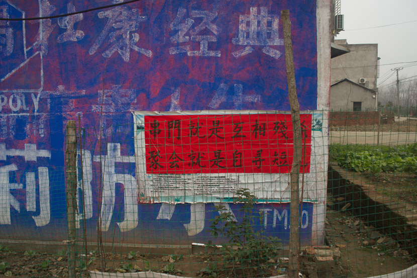 """A poster bearing the slogan, """"Seeing Each Other Is Mutual Slaughter; Going to a Party Is to Seek Your Own End"""" is displayed in a village near Tianmen, Hubei province, Feb. 1, 2020. Yang Chenhui for Sixth Tone"""
