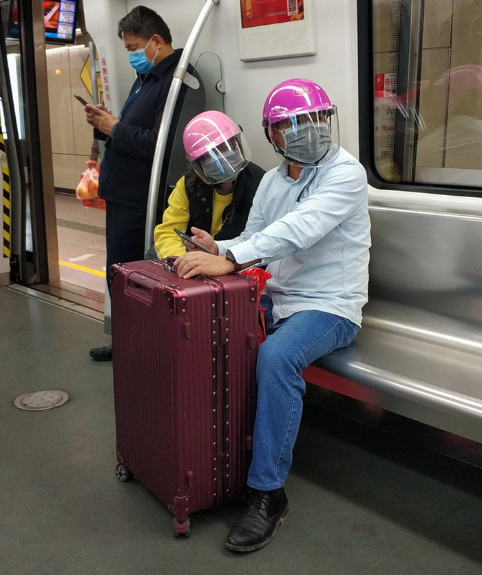 A couple wear helmets over their face masks on the subway in Guangzhou, Guangdong province, Jan. 29, 2020. Tan Qingju/Southern Metropolis Daily