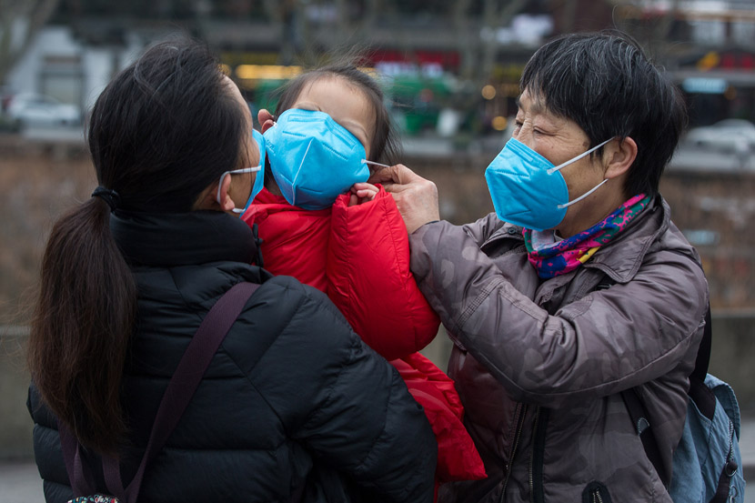A woman forces her granddaughter to wear a face mask in Hangzhou, Zhejiang province, Jan. 28, 2020. Chen Zhongqiu for Sixth Tone