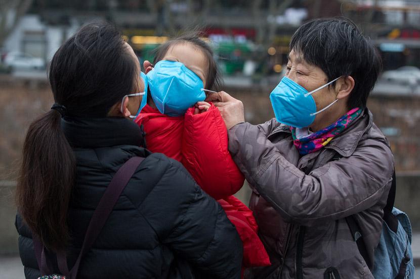 A woman forces her granddaughter to wear a face mask in Hangzhou, Zhejiang province, Jan. 28, 2020. Chen Zhongqiu for Sixth Tone