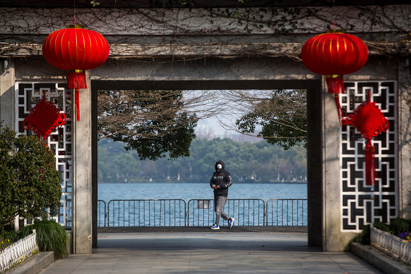 A tourist wearing a mask walks along the West Lake in Hangzhou, Zhejiang province, Jan. 30, 2020. Chen Zhongqiu for Sixth Tone