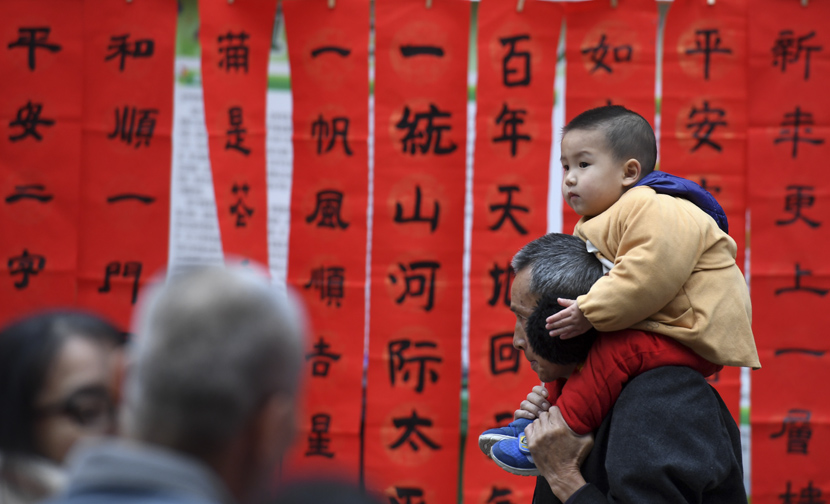 A boy perches on his grandfather's shoulders in front of spring couplets in Nanning, Guangxi Zhuang Autonomous Region, Jan. 18, 2020. Lu Boan/Xinhua