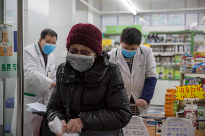 An elderly woman exits a pharmacy after purchasing five face masks in Shanghai, Feb. 5, 2020. Yi Chuan for Sixth Tone