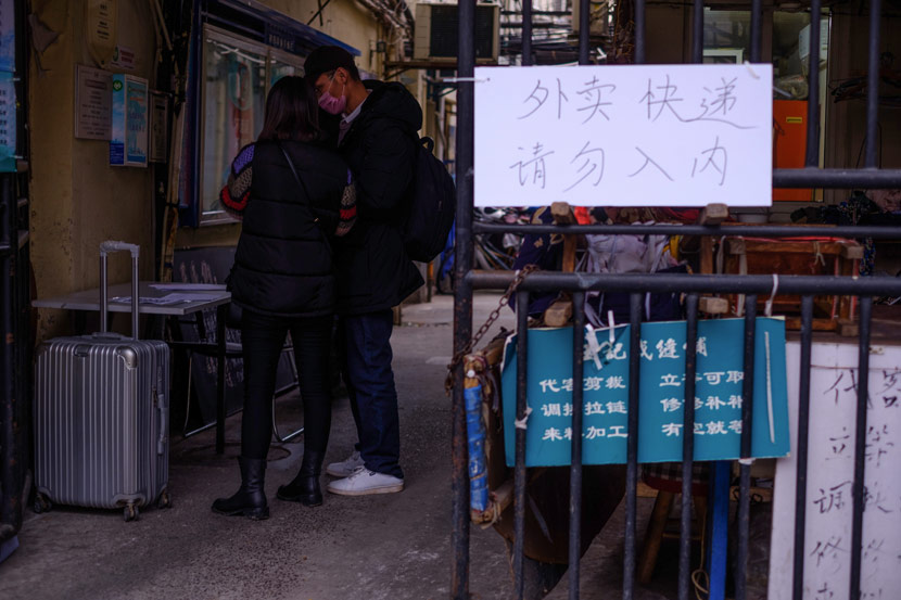 A man who has just returned to Shanghai fills out a registration form at the entrance of a residential complex, Shanghai, Feb. 5, 2020. Wu Huiyuan/Sixth Tone