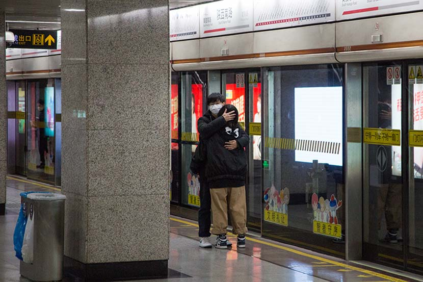A young couple embrace on the subway platform at South Shaanxi Road Station in Shanghai, Feb. 6, 2020. Shi Yangkun/Sixth Tone