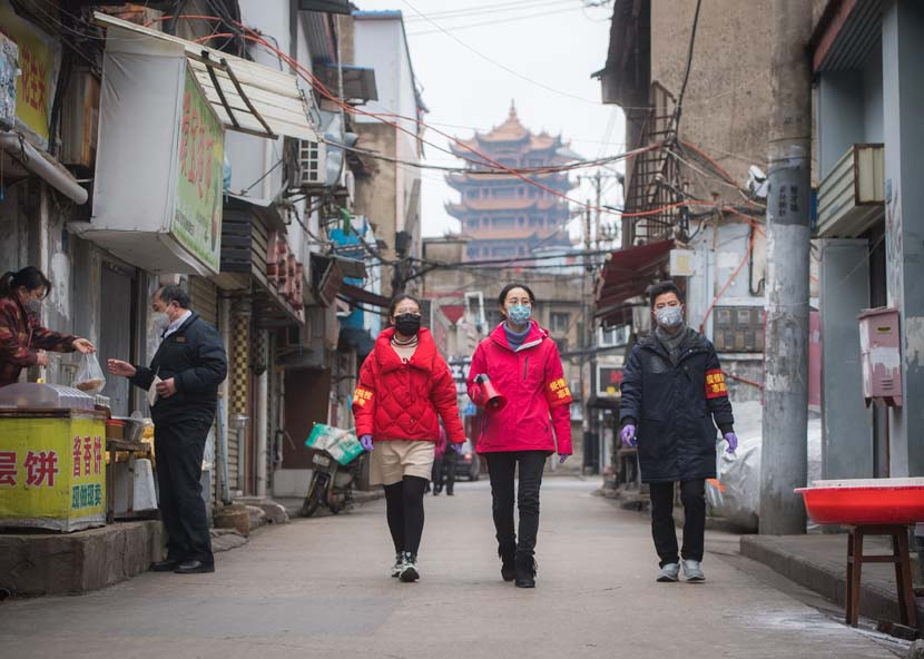 Community workers publicize anti-epidemic measures near Yellow Crane Tower in Wuhan, Hubei province, Feb. 7, 2020. Xinhua