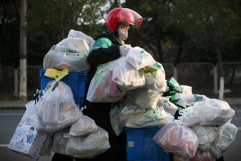 A delivery man carries daily necessities and fresh food in Shanghai, Feb. 9, 2020. Residents rely on delivery companies to send groceries, so they don't have to shop in crowded supermarkets during the novel coronavirus outbreak period. Zhu Weihui for Sixth Tone