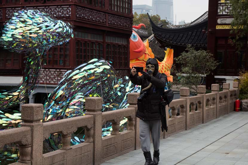 A man wearing a gas mask takes photos at Yu Garden during the Lantern Festival in Shanghai, Feb. 8, 2020. Shi Yangkun/Sixth Tone
