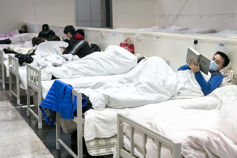 "A young man reads ""Origins of Political Order"" at a so-called shelter hospital designated for patients in Wuhan, Hubei province, Feb. 5, 2020. Xinhua"