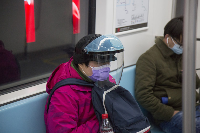 A woman wears a helmet outside her face mask on the subway in Shanghai, Feb. 10, 2020. Shi Yangkun/Sixth Tone