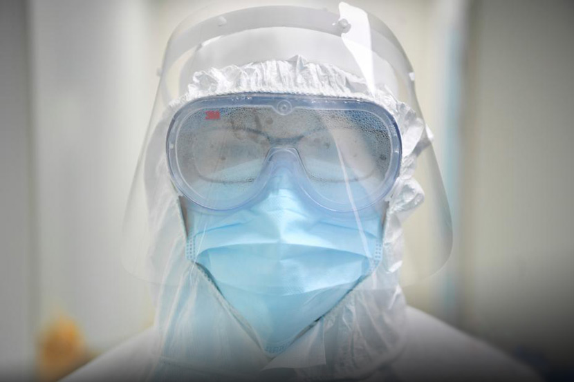 A medical worker in full protective gear, goggles steamed up, works at a hospital in Mengzi, Yunnan province, Feb. 1, 2020. Liu Ranyang/CNS