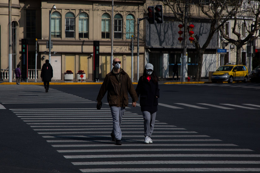 People wearing masks cross a road in Shanghai, Feb. 5, 2020. Shi Yangkun/Sixth Tone
