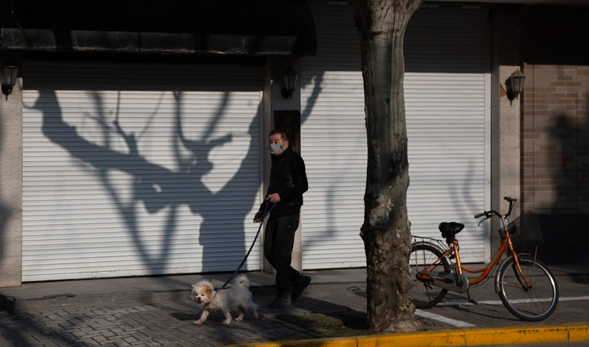 A man walks his dog past shuttered businesses in Shanghai, Feb. 12, 2020. Shi Yangkun/Sixth Tone