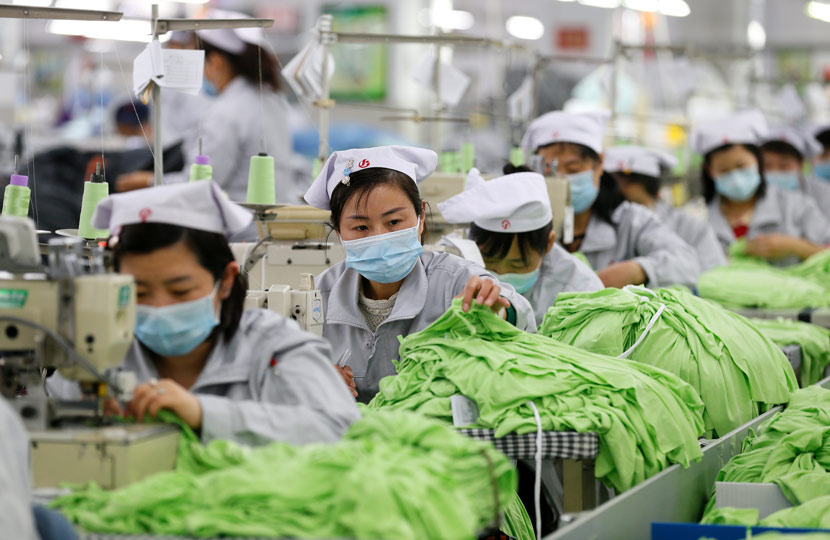 Workers wear face masks while sewing fabric at a reopened factory in Qingdao, Shandong province, Feb. 14, 2020. Liao Xiaopeng via Xinhua