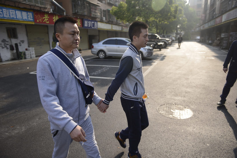 Sun Wenlin (right) holds his boyfriend's hand as they walk to the People's Court of Furong District for their lawsuit against the Bureau of Civil Affairs of Furong District, which rejected their marriage application in Changsha, Hunan province, April 13, 2016. IC