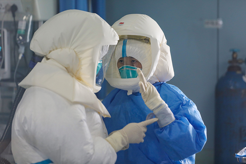 Medical workers in hazmat suits communicate using hand gestures at Jinyintan Hospital in Wuhan, Hubei province, Feb. 13, 2020. Yuan Zheng for Sixth Tone
