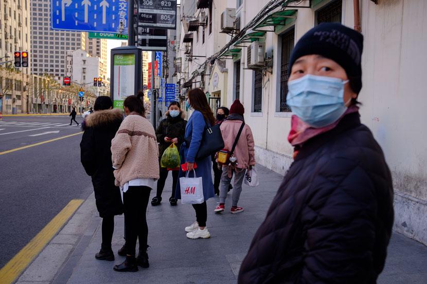 People wait at a bus stop in Shanghai, Feb. 4, 2020. Wu Huiyuan/Sixth Tone