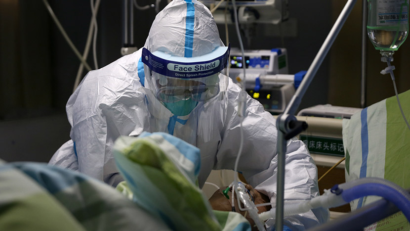 A medical worker in full protective gear attends to a patient at Zhongnan Hospital of Wuhan University, Hubei province, Jan. 23, 2020. Zheng Chaoyuan and Wei Jiaming for Sixth Tone