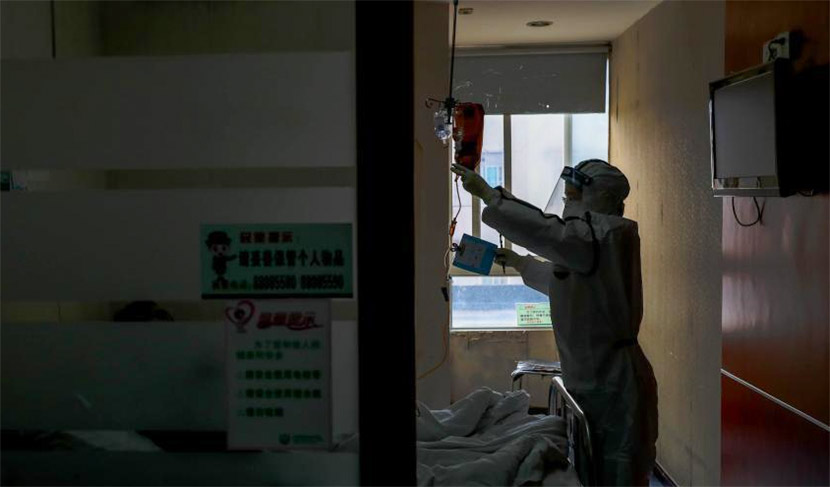 A medical worker checks on a patient at a hospital in Wuhan, Hubei province, Feb. 3, 2020. Zhang Chang/CNS