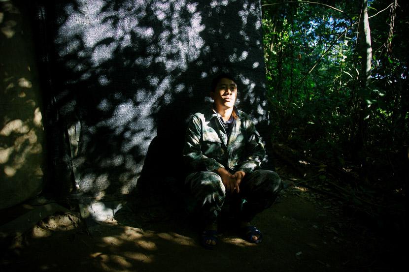 Li Du sits on a stool outside his bird pond in Yingjiang County, Yunnan province, Jan. 16, 2020. Li You/Sixth Tone