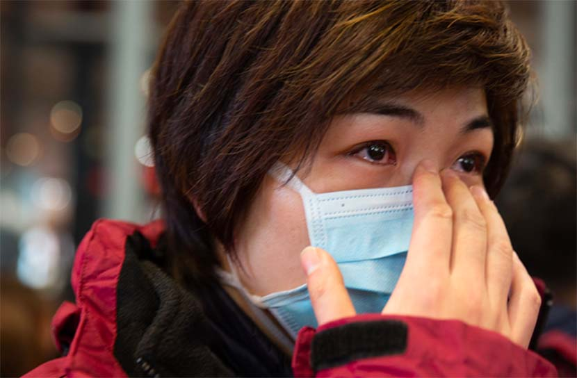 A nurse on her way to Wuhan to help with the emergency medical relief efforts bids farewell to her son on Lunar New Year's Eve at Shanghai Hongqiao International Airport, Feb. 24, 2020. From The Paper