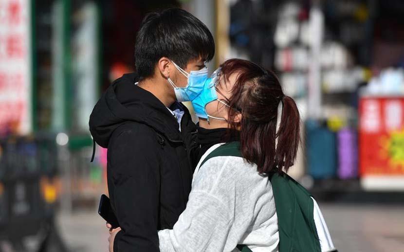 A couple wearing face masks kiss at a railway station in Kunming, Yunnan province, Feb. 17, 2020. Liu Ranyang/CNS