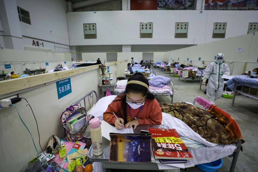 """A teenage coronavirus patient studies for the college entrance exams at a temporary """"shelterhospital"""" in Wuhan, Hubei province, Feb. 18, 2020. Yuan Zheng/Changjiang Daily"""