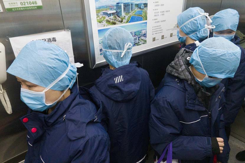 Medical workers stand with their backs to one other to avoid the risk of cross-infection as they take an elevator at the Optics ValleyBranch of Tongji Hospital in Wuhan, Hubei province, Feb. 20, 2020. Xinhua