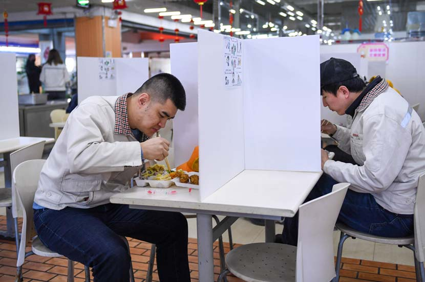 Workers eat lunch at the cafeteria of Jinhe TransportationEquipmentCo.Ltd. in Changchun, Jilin province, Feb. 17, 2020. Some company canteens are using partitionsto keep staff separated while eating and reduce the risk of cross-infection. Xinhua