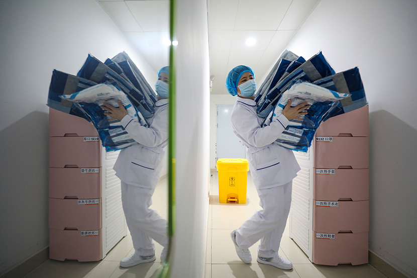 A medical worker carries protective clothing kits at Jinyintan Hospital in Wuhan, Hubei province, Feb. 13, 2020. Yuan Zheng for Sixth Tone