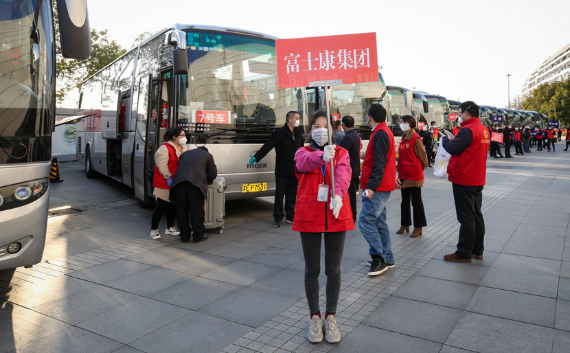 A bus picks up Foxconn employees returning to work from other provinces at Kunshan South Station in Kunshan, Jiangsu province, Feb. 20, 2020. Zhou Zhou/IC