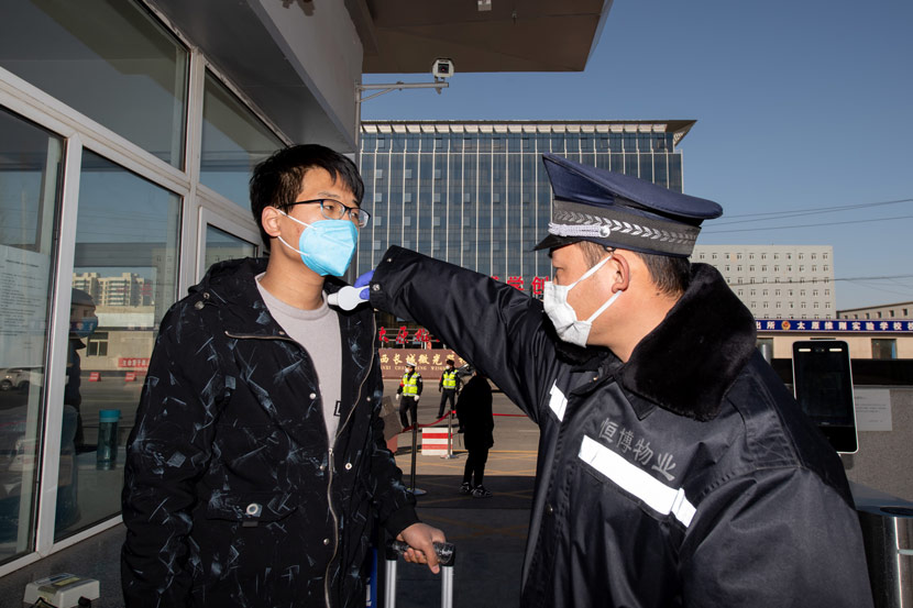 A guard tests an employee's temperature at the entrance of a factory in Taiyuan, Shanxi province, Feb 22, 2020. Hu Yuguang/IC