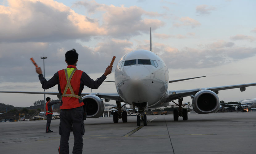 A ground control worker directs a commercial jet at an airport in Sanya, Hainan province, Feb. 24, 2020. Sha Xiaofeng/IC