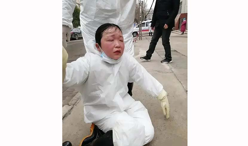 A medical worker faints from exhaustion outside a hospital in Hanchuan, Hubei province, February 2020.