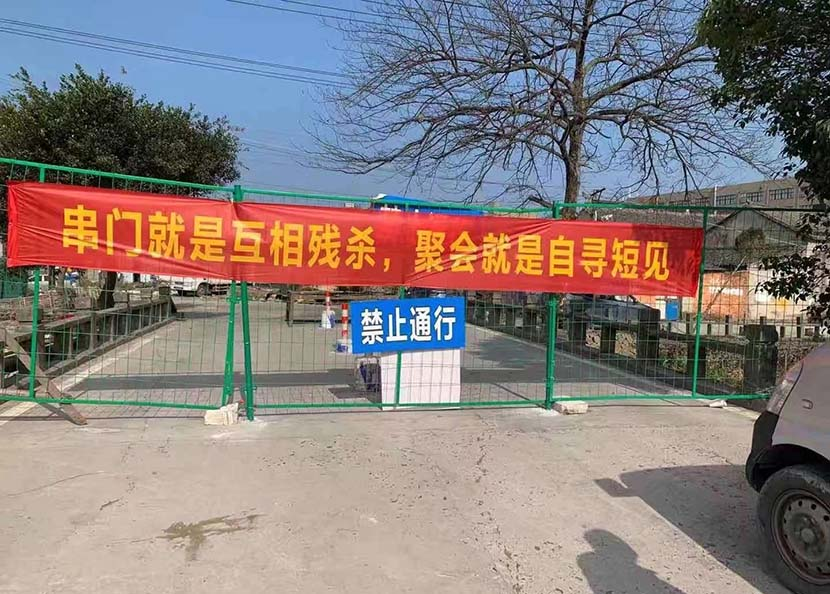"A banner bearing the slogan, ""by visiting others' homes, you're murdering each other; by partying, you're committing suicide"" hangs outside a rural residential compound in Wenzhou, February 2020. Courtesy of Duoduo"