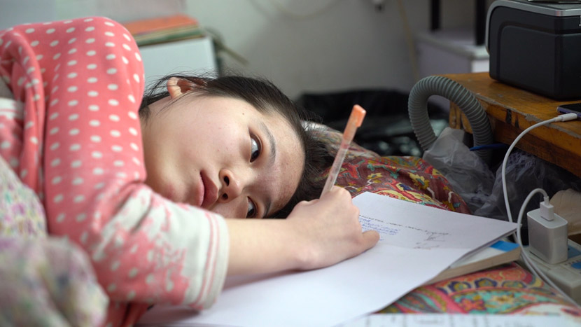 Lu Liang finishes her homework in bed at her home in Heze, Shandong province, March 2019. Li Yang and Wang Haowei for Sixth Tone